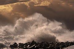 Wave splash at sunset. Big stormy sea wave splash at orange winter sunset Stock Image