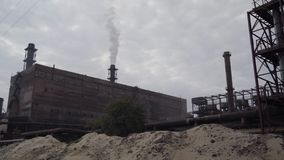 A big stovepipe smokes on the mining and processing plant