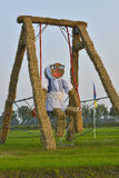 Big straw doll in a swing Stock Photo