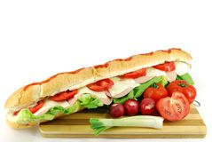 Big sub sandwich. With green salad and vegetables Stock Photography