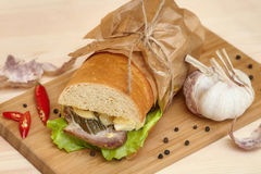 Big sub sandwich baguette with ham on wooden cutting board. Big sub sandwich baguette with ham, chili and lettuce on wooden cutting board, closeup stock image