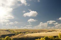 Big sun cloudy blue sky above an autumn landscape Royalty Free Stock Image