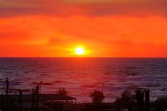 Big sun over sea sunset red horizon orange colored sky Stock Photography