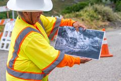 BIG SUR, CA - AUGUST 3, 2017: Woman shows winter landslide damag. E in Cabrillo Highway. The road is still under construction Stock Photo