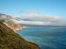 Big Sur California coast, bridge, beach, rocks, clouds, and surfing waves royalty free stock image