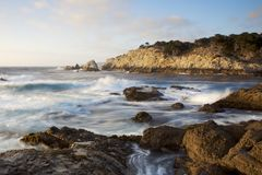 Big Sur coastal scene. Crashing Pacific Ocean waves break on a rocky shore at dusk. A headland is visible in the distance with warm sunlight lighting the pale stock photo