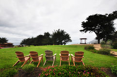 BIG SUR, KALIFORNIEN, CA, USA: Fünf Sitze auf dem grünen Gras nahe dem Ozean Stockfoto