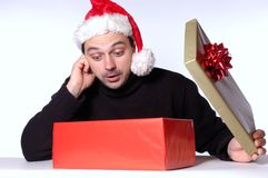 Big surprise. Man with santa hat looks surprised in his gift box Royalty Free Stock Photos