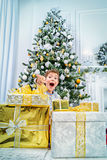 Big surprise. Funny boy in pajama expressing big surprise sitting near the Christmas tree and Christmas gifts. Time for miracles Royalty Free Stock Images