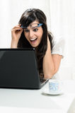 Big surprise in Laptop. Very happy young woman gets a big surprise in her computer and she raises her glasses in amazement Royalty Free Stock Images