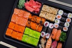 Big sushi set in black plastic box. On black background/ top view close up macro shoot Stock Image