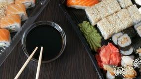 Big sushi set with variety of sushi rolls, maki, nigiri, gunkan on a stylish dark background. Soy sauce and bamboo. Big sushi set with variety of sushi rolls stock video footage