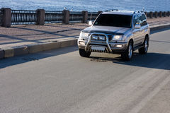Big suv car drives on asphalt. Road near river  part of luxury cars series Royalty Free Stock Image