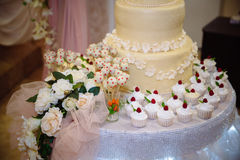 Big sweet multilevel wedding cake decorated with flowers. Concept of candy bar on party Royalty Free Stock Images