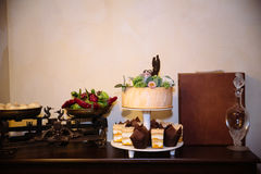 Big sweet multilevel wedding cake decorated with flowers. Concept of candy bar on party Stock Photos