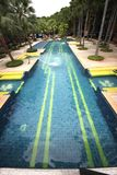 A big swimming pool with clear water and seats in water in the Nong Nooch tropical botanic garden near Pattaya city in Thailand Stock Photos