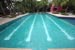 A big swimming pool with clear water and seats in water in the Nong Nooch tropical botanic garden near Pattaya city in Thailand Stock Photography