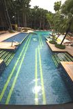 A big swimming pool with clear water and seats in water in the Nong Nooch tropical botanic garden near Pattaya city in Thailand Royalty Free Stock Images