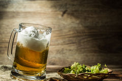 Big tankard of beer standing on empty wooden background Royalty Free Stock Photography