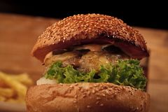 Big Tasty burger. Big tasty appetizing fresh burger of green lettuce red tomato cheese and bacon slice meat cutlet and white bread bun with sesame seeds closeup royalty free stock images