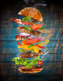 Big tasty burger with flying ingredients. Big tasty home made burger with flying ingredients royalty free stock photography