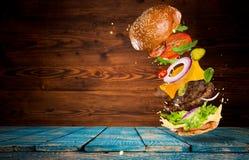Big tasty burger with flying ingredients. Big tasty home made burger with flying ingredients stock photo
