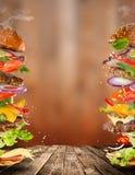 Big tasty burger with flying ingredients. Big tasty home made burger with flying ingredients royalty free stock photos