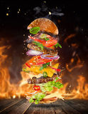 Big tasty burger with flying ingredients. Big tasty home made burger with flying ingredients. Fire flames on background royalty free stock photos
