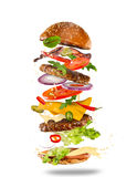 Big tasty burger with flying ingredients. stock photo