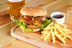 Big tasty burger and fries with beer on backround on the wooden table. Big tasty burger and fries with beer on background on the wooden table. fried bacon and royalty free stock photo