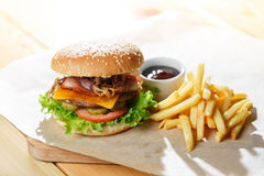 Big tasty burger and fries on the wooden table. Fried bacon and onion rings. Lettuce and slices of tomato stock image