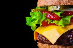 Big tasty hamburger or cheeseburger on black background with grilled meat, cheese, tomato, bacon, onion. Burger closeup.  stock photo
