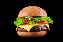 Big tasty hamburger or cheeseburger isolated on black background with grilled meat, cheese, tomato, bacon, onion. Burger. Closeup stock photo