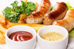 Big tasty sausages with French fries Royalty Free Stock Image