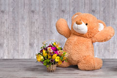 Big Teddy bear with a basket of spring flowers. Spring concept .Teddy bear with a basket of flowers royalty free stock image
