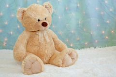 Big teddy bear on furry white blanket Stock Photography