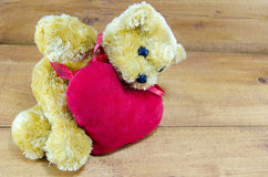 Big teddy bear lying on a red heart Royalty Free Stock Image