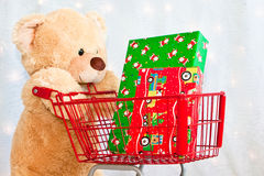 Big teddy bear with shopping cart and presents Royalty Free Stock Photography