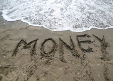 Text MONEY on the sand of the sea almost erased by the wave of t. BIG text MONEY on the sand of the sea almost erased by the wave of the sea Royalty Free Stock Photography