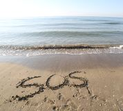 SOS on the sand of the beach. Big text SOS on the sand of the beach stock images
