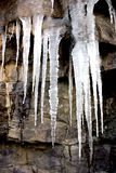 The big thaw. Melting icicles on a rocky roadside embankment royalty free stock photo
