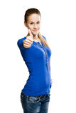 Big thumbs up. Portrait of a slender young brunette showing big thumbs up royalty free stock photography