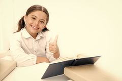 A big thumbs up to home schooling. Little girl reading lesson book at home. Adorable pupil develop reading skills. Small royalty free stock images