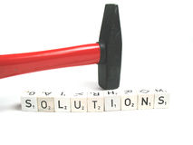 Big time solutions. A hammer behind the word solutions Royalty Free Stock Photo
