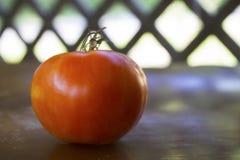 Big tomato (Solanum lycopersicum) sitting on a wooden surface stock photography