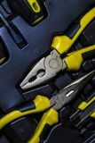 Big tool kit of black and yellow colors for the house in a box. Flat-nose pliers, screw-drivers, stationery knife and nippers. stock image