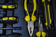 Big tool kit of black and yellow colors for the house in a box. Flat-nose pliers, screw-drivers, stationery knife and nippers. Big tool kit of black and yellow royalty free stock image