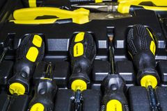 Big tool kit of black and yellow colors for the house in a box. Flat-nose pliers, screw-drivers, stationery knife and nippers. Repair royalty free stock photography