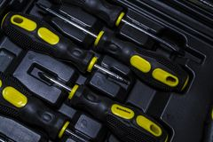 Big tool kit of black and yellow colors for the house in a box. Flat-nose pliers, screw-drivers, stationery knife and nippers. royalty free stock image