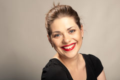 Big toothy smile. Portrait of  beautiful young woman with red lips  over gray. Big toothy smile Royalty Free Stock Image